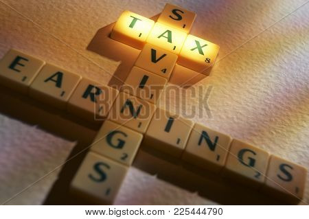 Cleckheaton, West Yorkshire, Uk: Scrabble Board Game Letters Spelling The Words Saving Tax Earnings,