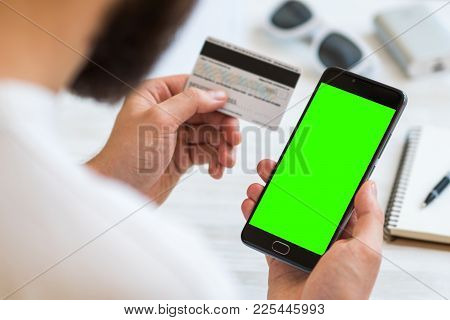 A Black Smartphone With Green Screen For Chroma Key Compositing And A Credit Card In The Hands Of A