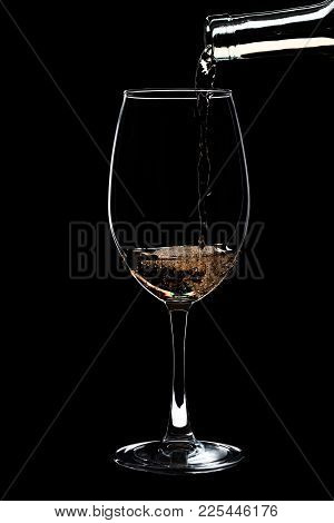 A Large Glass Of White Wine Is Pouring Wine From A Bottle Of White. Filmed In Close-up Glass, Where