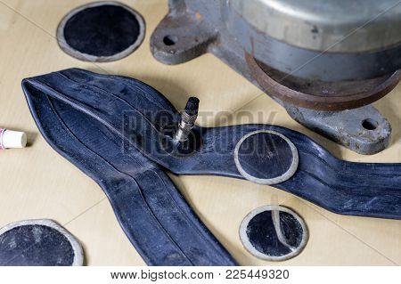 Repairing A Bicycle Tube In A Tire Bonding Workshop. Detek Repair Station In The Vulcanization Works