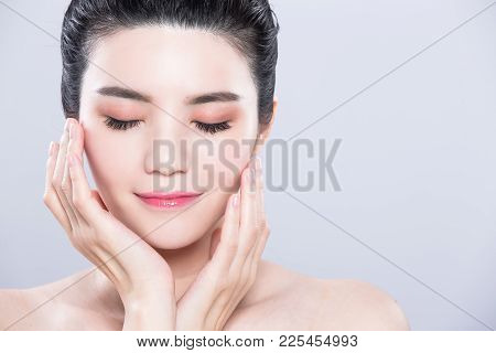 Woman Close Eyes And Touch Face With Beauty Skin Care Concept On The Gray Background