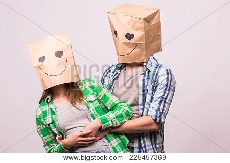 Love Couple Covering Their Faces With Paper Bag Over White Background.