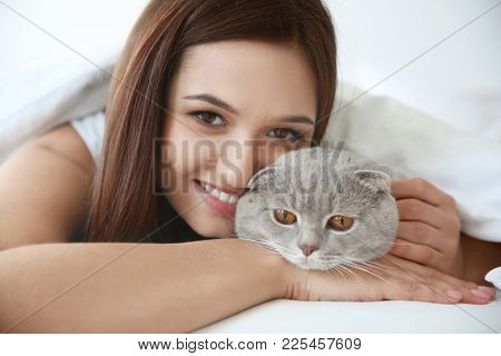 Young woman with cute pet cat in bed at home