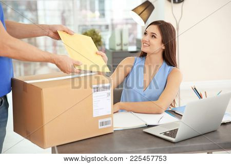 Woman receiving parcels from courier indoors