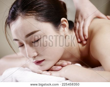 Close-up Of Face Of A Beautiful Young Asian Woman Lying On Front On Bed Receiving Massage In Spa Sal