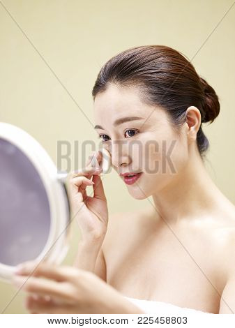 Beautiful Young Asian Woman Looking In The Mirror While Cleansing Face With A Sponge