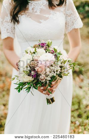 Bride Holds In Hands A Rustic Wedding Bouquet With White Dahlias, Peonies, And Greens. Artwork. Clos