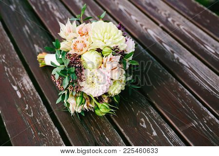 Bridal Bouquet Lie On The Brown Wooden Table. Artwork. Side View Artwork. Top View Copy Space