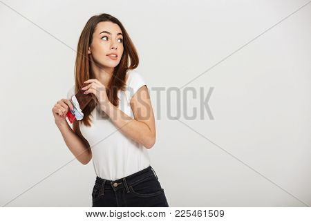 Portrait of an ashamed young woman hiding chocolate bar isolated over white background
