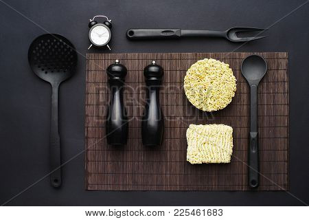 Instant Vermicelli And Black Kitchen Accessories On A Black Background. Laconic Concept. Flat Lay. T