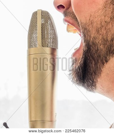 An Old Fashioned Gold Microphone Is Set Infront Of A Males Face. The Male Is Screaming Into The Micr
