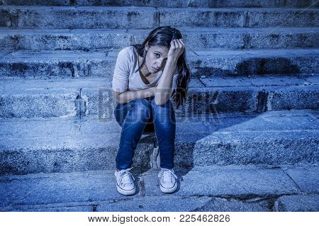 Expressionist Edited Portrait Of Young Sad And Depressed Woman Or Teen Girl Sitting Lonely At Street