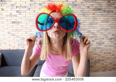 Young woman in funny disguise posing on brick wall background. April fool's day celebration