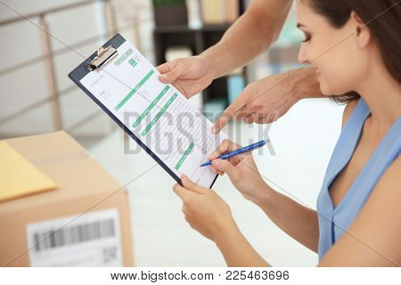 Woman signing documents after receiving parcel from courier
