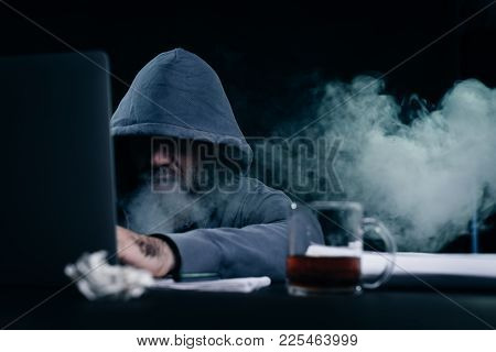 Male Hacker Sitting At A Table And Smoking