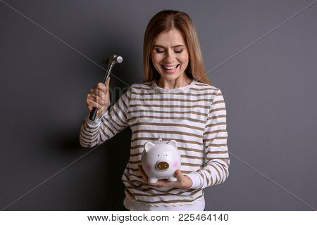 Young woman holding hammer over piggy bank on grey background