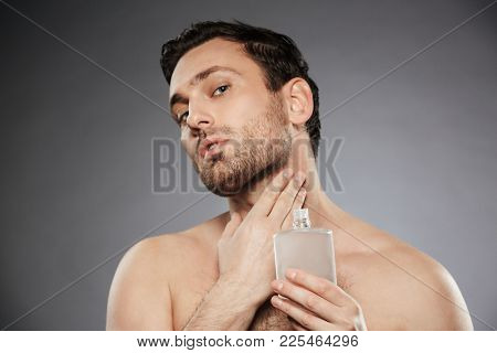Portrait of masculine sexual man putting perfume aftershave on his neck isolated over gray background
