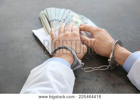 Doctor in handcuffs with bribe at workplace
