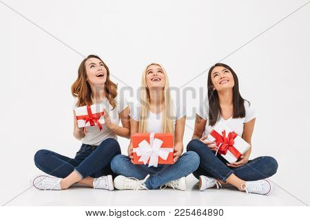 Photo of three young cute girls friends sitting isolated over white background looking aside holding surprise gifts boxes.