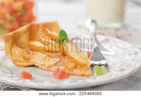 Plate with piece of tasty apple tart on table, closeup