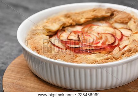 Baking dish with freshly cooked apple tart on table, closeup
