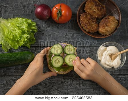 The Girl Puts The Cucumber Slices On A Cooked Hamburger. Cooking Hamburger For School Lunch Child.