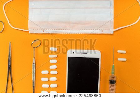 On The Orange Surface Is A Smartphone, Medical Instruments And Pills