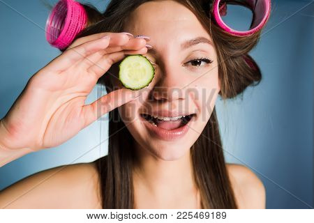 Happy Woman With Big Curlers On Her Head Holds A Cucumber In Her Hands