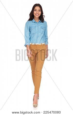happy young casual woman walking forward and smiles on white background