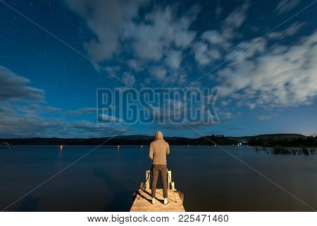 Young Male Photographer Taking Photo On Jetty By The Lake At Night Time. Stargazing Photography In N
