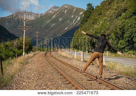 Young Asian Male Photographer Walking On Railway With Mountain Scenery Background. Travel In Summer