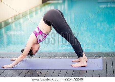 Beautiful Young Asian Woman Doing Yoga Exercise With Downward Facing Dog Posing (adho Mukha Svanasan