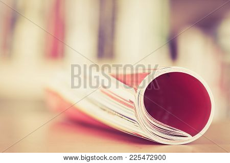 Close Up Edge Of Colorful Magazine Stacking Roll With  Blurry Bookshelf Background For Bublication A
