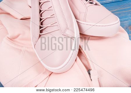 Womanly Pink Leather Shoes And Sweatshirt Or Hoodie On Old Blue Boards