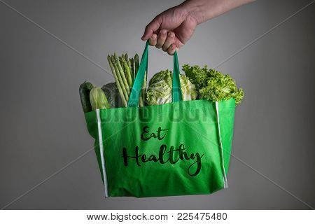 Close Up A Hand Holding Green Grocery Bag With Eat Healthy Text Of Mixed The Organic Green Vegetable