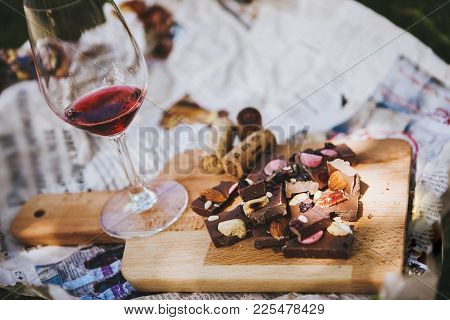 Glass With Red Wine And Pieces Of Chocolate With Nuts And Raisins Stands On Cutting Board On Backgro