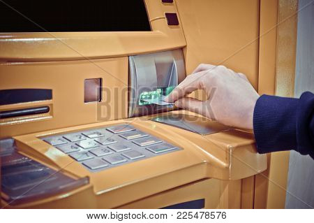 Close-up Of Woman's Hand Inserting Debit Card Into An Atm Machine
