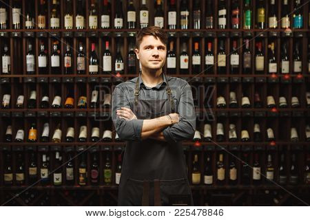 Barkeeper In Apron Stands In Wine Cellar With Large Shelves Full Of Closed Bottles With Exquisite Al