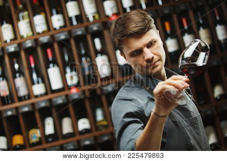 Bokal Of Red Wine On Background Of Male Sommelier Appreciating Color, Quality, Flavor And Sediments