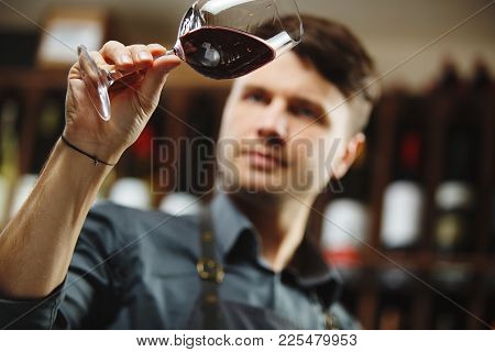 Bokal Of Red Wine On Background Of Male Sommelier Look Appreciating Color, Quality, Flavor And Sedim