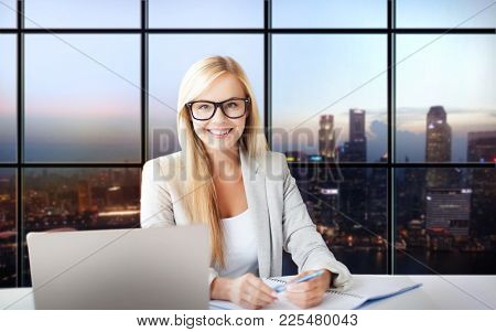 business and people concept - happy businesswoman with documents and laptop computer at office over singapore city skyscrapers background