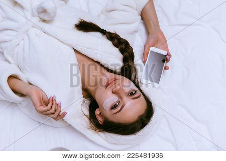 Beautiful Young Girl In A White Terry Dressing Gown Lying On A Bed, Under The Eyes Of White Patches