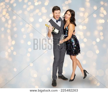 celebration and holidays concept - happy couple with bottle of non alcoholic champagne and wine glasses at party over festive lights background