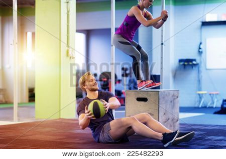 fitness, sport, training, exercising and people concept - happy woman and man with medicine ball doing curl ups and box jumps in gym