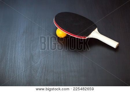 Table Tennis Or Ping Pong Racket And Ball On A Black Background