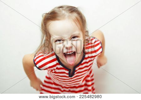 Angry Little Girl Shows Her Tongue In Funny Grimace With Body Leaned Toward Camera, Dressed In Strip