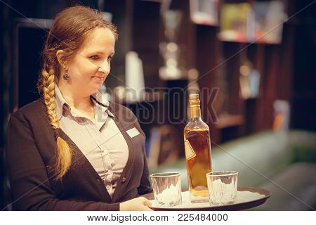 A Barmaid Girl Carries A Bottle Of Whiskey With Glasses On A Tray To The Client Of The Hotel Bar. Th