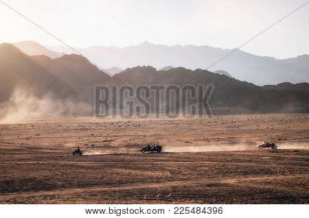 Buggy And Atv Quads Races In Sinai Desert At Sunset. Egyptian Landscape With Off-road Vehicles And D