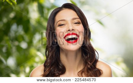 beauty, organic, make up and people concept - happy laughing young woman with red lipstick over green natural background
