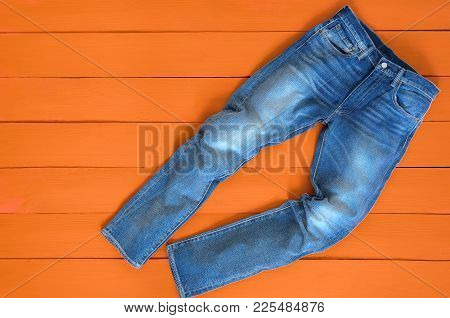 Blue Mens Jeans Denim Pants On Orange Background. Contrast Saturated Color. Fashion Clothing Concept